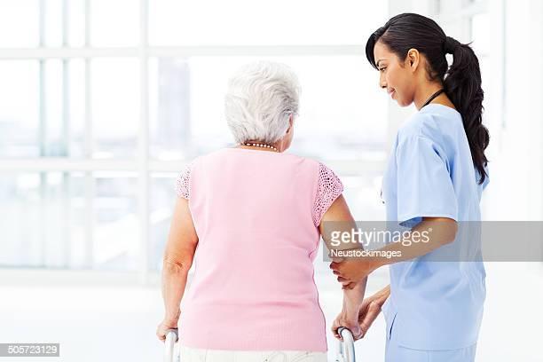 Nurse Assisting Senior Patient With Walker In Nursing Home