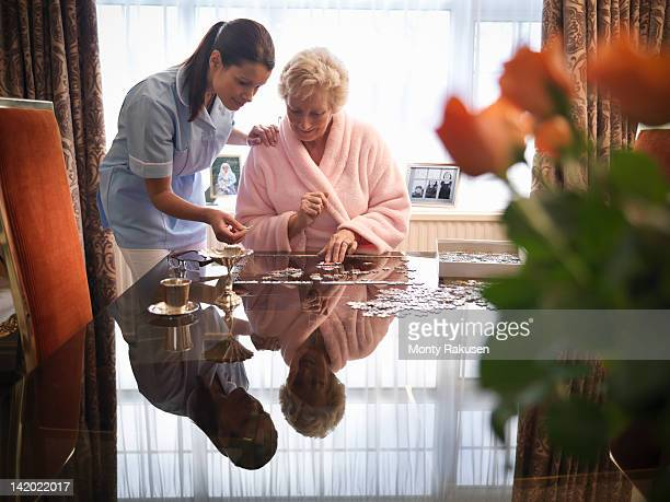 Nurse assisting senior woman to complete jigsaw puzzle