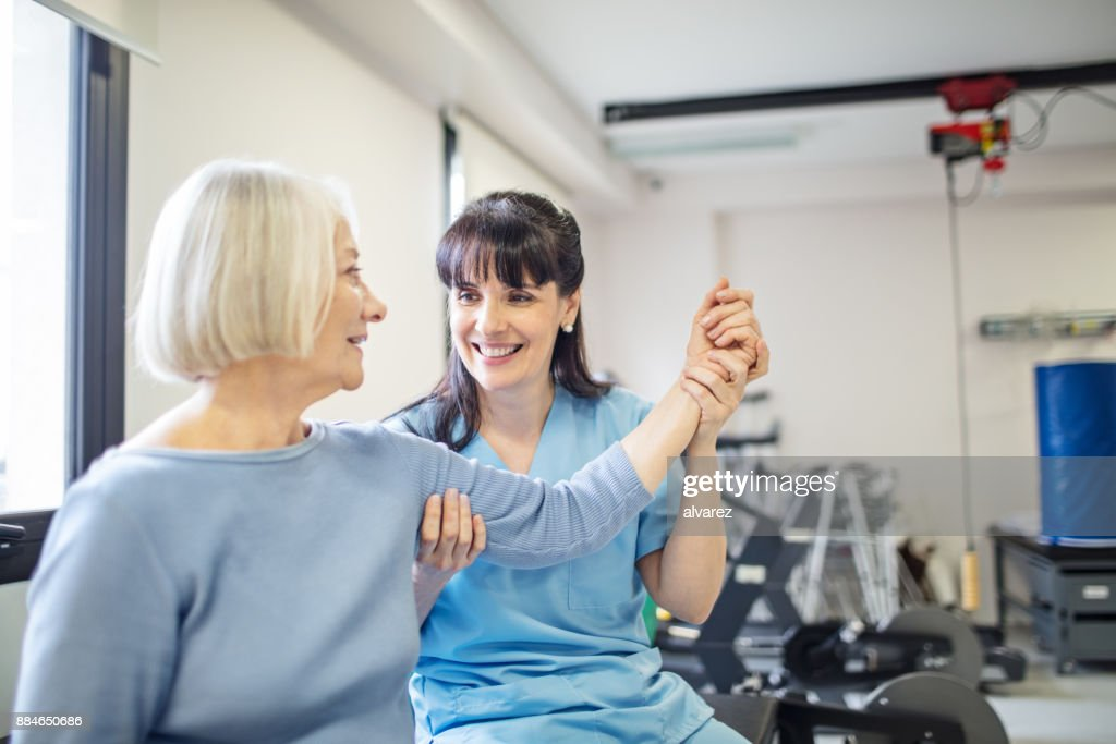 Nurse assisting senior woman with hand exercise : Stock Photo