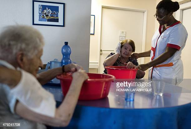 A nurse assists a woman cooling off with a bucket of water at a residential care home for dependent elderly people in Lyon on July 2 2015 as a...