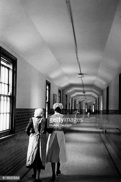 Nurse assists an old woman along a corridor in a psychiatric hosiptal.