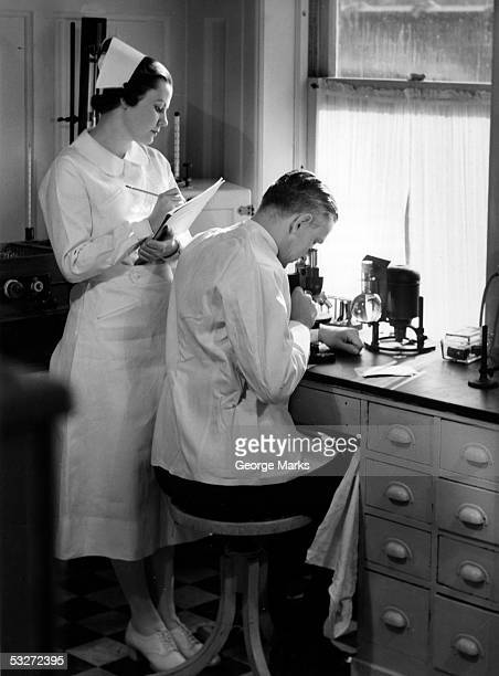 nurse assists doctor's research in lab - 20th century stock pictures, royalty-free photos & images