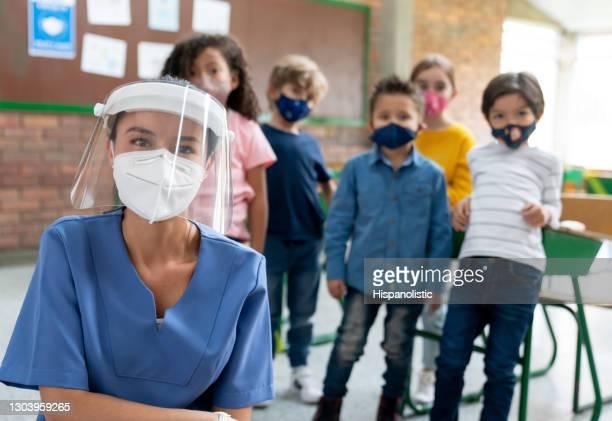 enfermeira de uma escola durante a pandemia covid-19 cercada por crianças usando máscaras faciais - instruções - fotografias e filmes do acervo