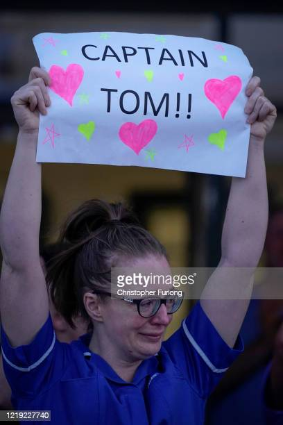 A nurse at Aintree University Hospital sheds a tear and as she pays tribute to super fundraiser Captain Tom Moore during the Clap for Our Carers and...