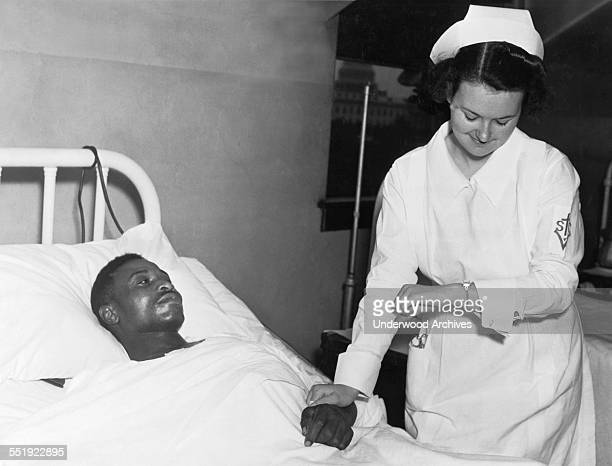 A nurse at Providence Hospital taking a man's pulse who had had surgery to repair a stab wound in his heart Washington DC July 20 1937