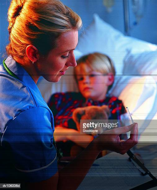 Nurse at sick childs bedside, checking temperature on thermometer