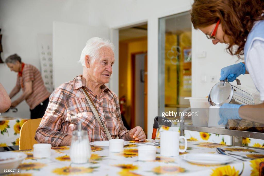 Verpleegkundige op de Care Center serveert ontbijt aan de ingezetene : Stockfoto