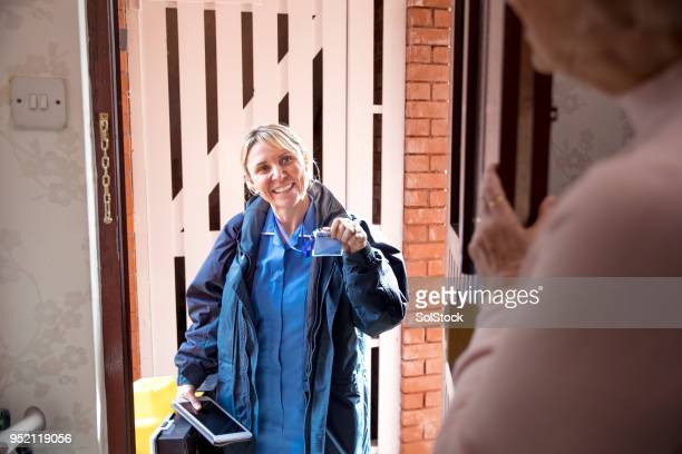 nurse at the door making a house call - visit stock pictures, royalty-free photos & images