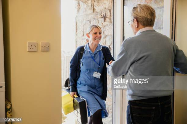 nurse at the door making a house call to a senior man - visita imagens e fotografias de stock