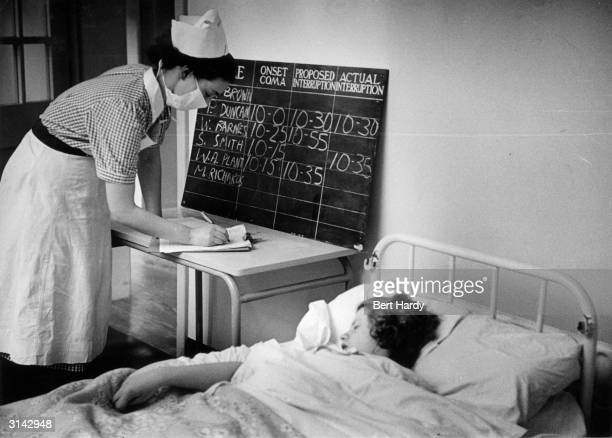 A nurse at the Netherne Mental Hospital near Coulsdon Surrey logs the times that a patient's coma is induced by insulin and interrupted by a dose of...