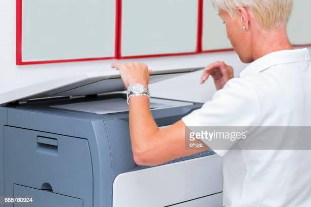 Infirmière à work.using photocopieuse, copiing résultats médicaux