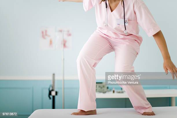 Nurse balancing on top of examination table, cropped