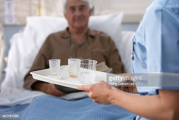 nurse bringing a tray of medication to a senior, male patient lying in bed - infermiera foto e immagini stock