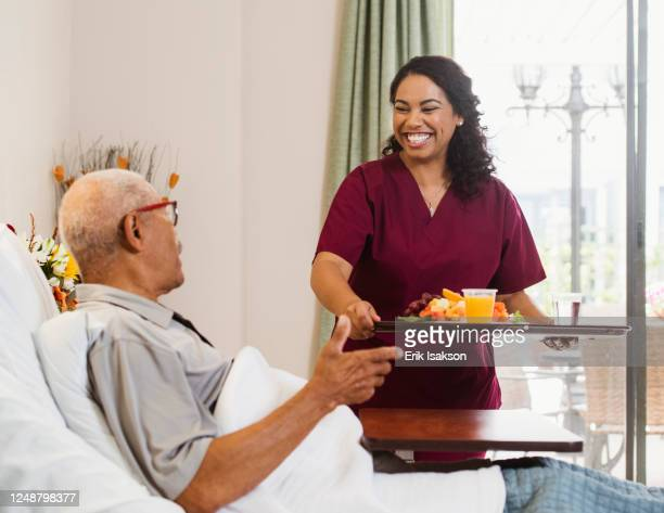 nurse bringing healthy meal to senior man in bed - leaning disability stock pictures, royalty-free photos & images
