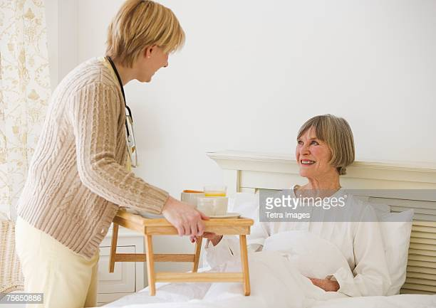 Nurse bringing senior woman breakfast in bed
