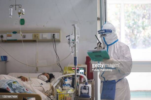 Nurse Cao Shan working in the isolation ward, communicates with a co-worker on the talkie-walkie in Jinyintan Hospital, designated for COVID-19...