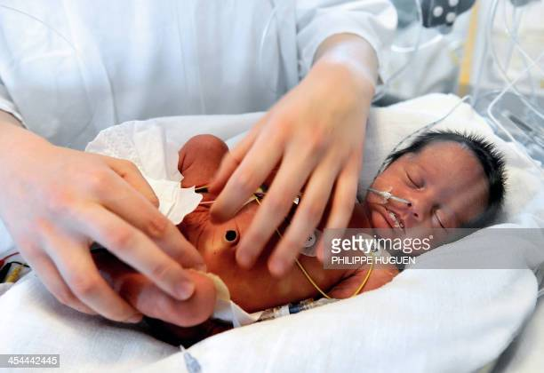 A nurse cares for a premature baby in an incubator at the neonatal ward of the Centre Hospitalier de Lens in Lens northern France on December 4 2013...