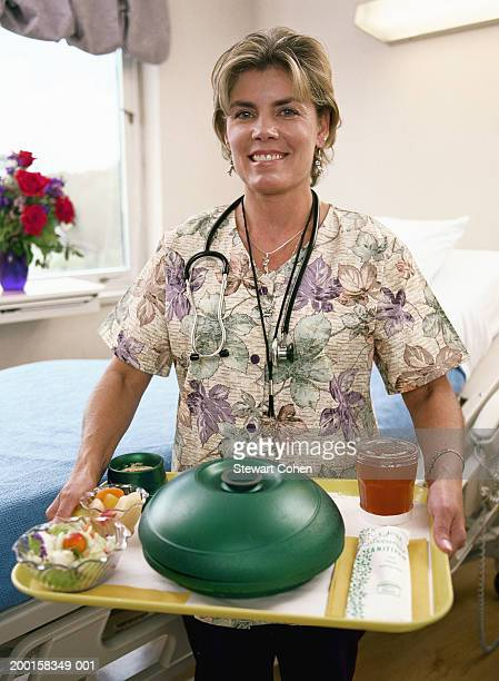 Nurse carrying tray of food in hospital room