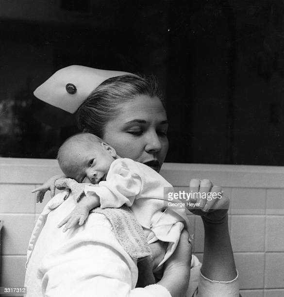 A nurse burping a baby after he has been fed