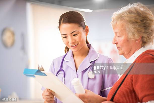nurse chats to senior patient - outpatient care stock pictures, royalty-free photos & images