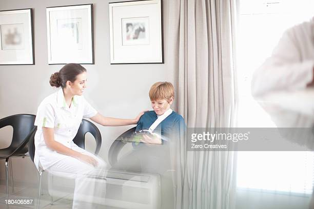 Nurse chatting to young patient in hospital reception