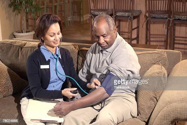 nurse checking blood pressure of patient - thinkstock foto e immagini stock