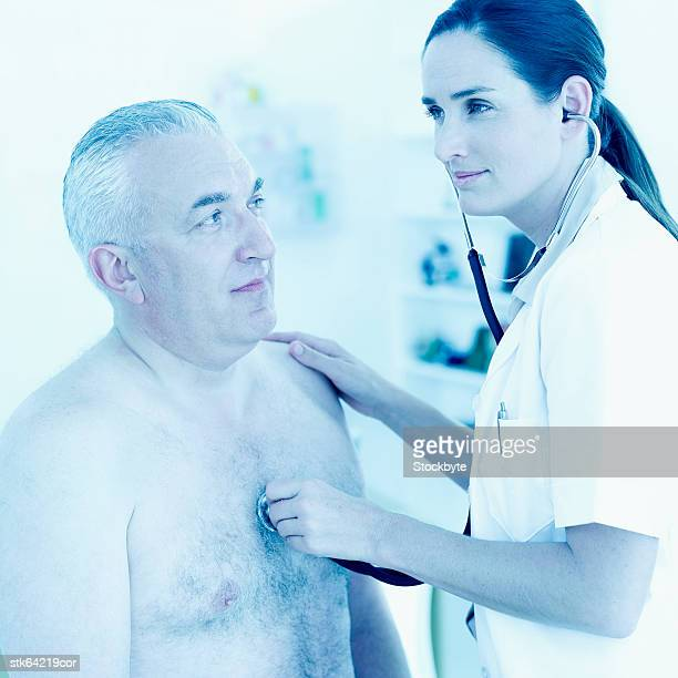 nurse checking heart beat of elderly man with a stethoscope - female hairy chest stock pictures, royalty-free photos & images
