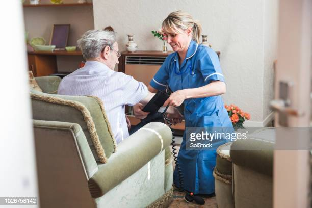 nurse checking her patient's blood pressure - social services stock photos and pictures
