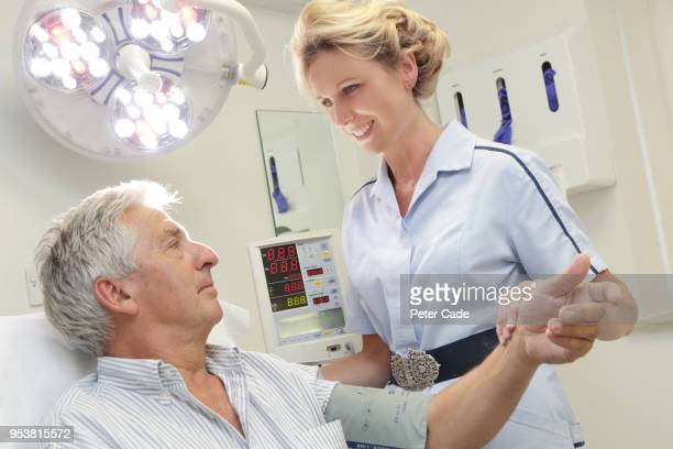 Nurse checking mans pulse
