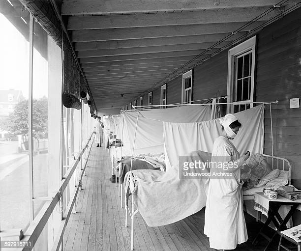 Nurse checking on a patient at the Walter Reed Hospital Flu Ward during the influenza pandemic, Washington DC, circa 1918.