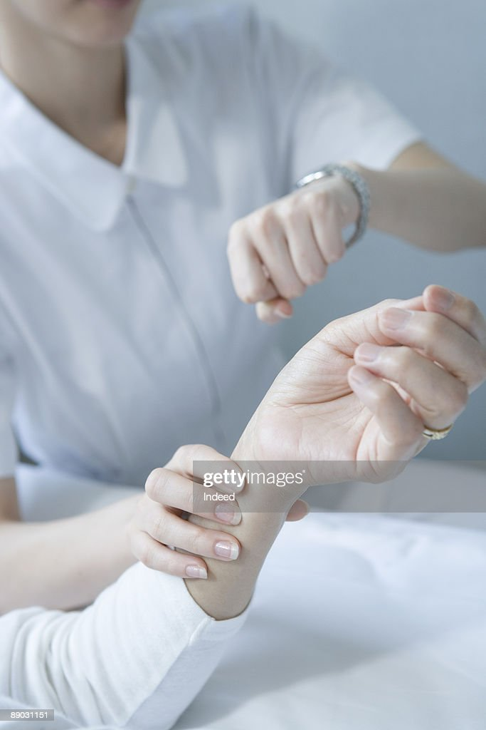 Nurse checking patients pulse in office - Stock Photo