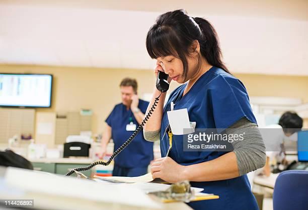 Nurse checks notes while talking on phone