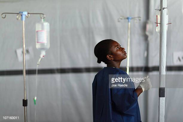 A nurse checks the intravenous solution while treating patients for cholera in an International Red Cross cholera treatment facility in the slum...