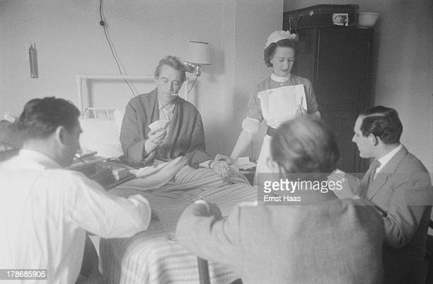 A nurse checks the pulse of American film director and screenwriter John Huston as he plays cards with friends from his hospital bed 1953...