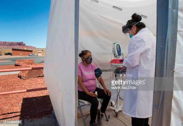 Nurse checks vitals from a Navajo Indian woman complaining of virus symptoms, at a COVID-19 testing center at the Navajo Nation town of Monument...