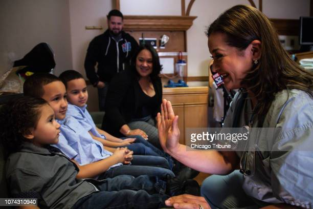 Nurse Claudia Lopez right visits with Jacob Roman left and his brothers Alex Jordan and their parents Vicelis Negron and Alexander Roman on Dec 10...