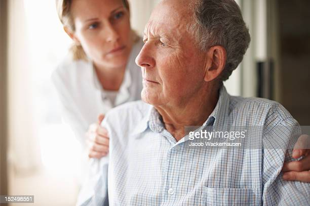 Nurse comforting a worried senior man