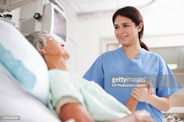 nurse comforting patient in hospital bed - old woman in sick bed stock photos and pictures