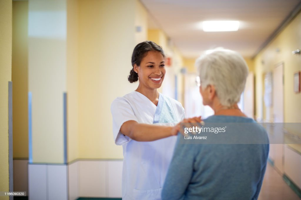 Nurse consoling a senior woman in hospital hallway : Stock Photo