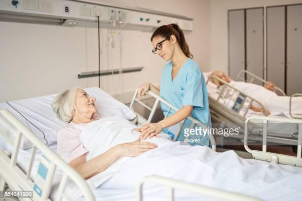 Infirmière femme senior consolante, couché dans son lit d'hôpital