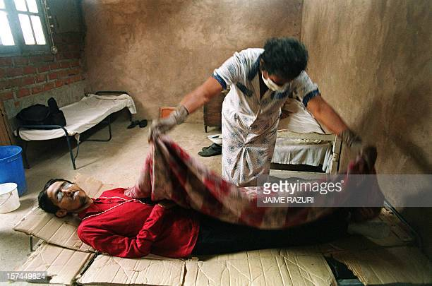 Nurse covers the dead body of Rigo, a 28-year-old male prostitute after he died from AIDS, 25 June 1993 in Lima. Rigo spent four years in this small...