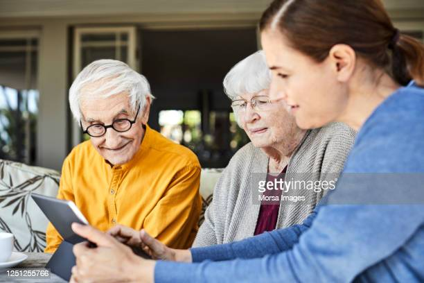 nurse discussing with senior couple over tablet pc - care stock pictures, royalty-free photos & images