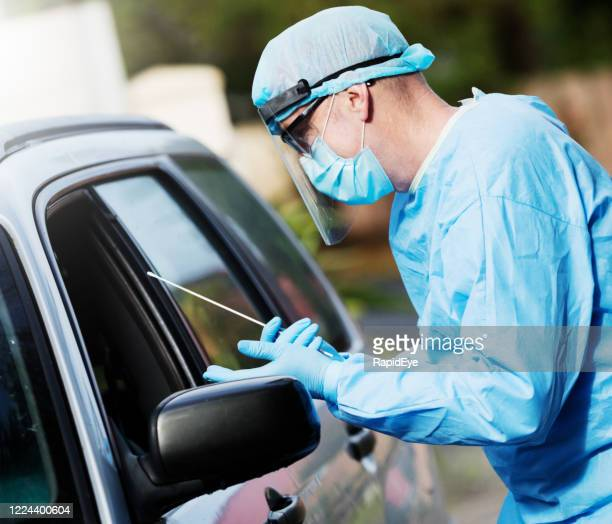 nurse, doctor or lab worker approaches car with swab to administer covid-19 test during coronavirus pandemic - coronavirus testing stock pictures, royalty-free photos & images