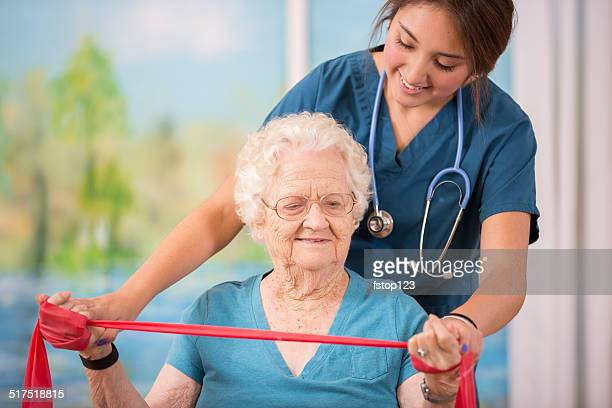 Enfermeira não Fisioterapia com a mulher idosa doente. Braço de reforço.