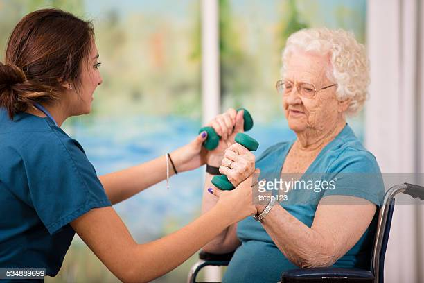 Nurse does physical therapy with senior woman patient. Arm strengthening.