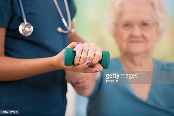 Krankenschwester ist Physiotherapie mit senior Frau geduldig. Arm Stärkung.