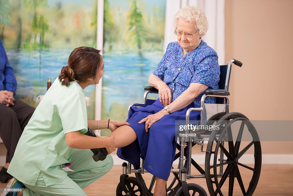 Nurse does physical therapy with senior woman patient. Leg strengthening. : Stock Photo