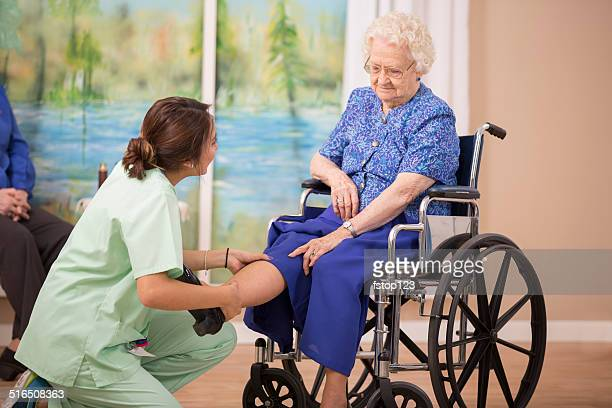 Nurse does physical therapy with senior woman patient. Leg strengthening.