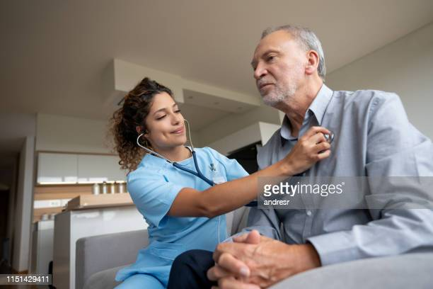 nurse doing a medical exam on a senior patient at home - human heart stock pictures, royalty-free photos & images