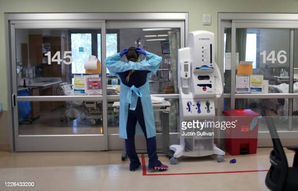 A nurse dons personal protective equipment as she prepares to enter the room of a coronavirus COVID19 patient in the intensive care unit at Regional...